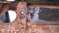 Rusted body mount brace on bottom of brake reservoir well